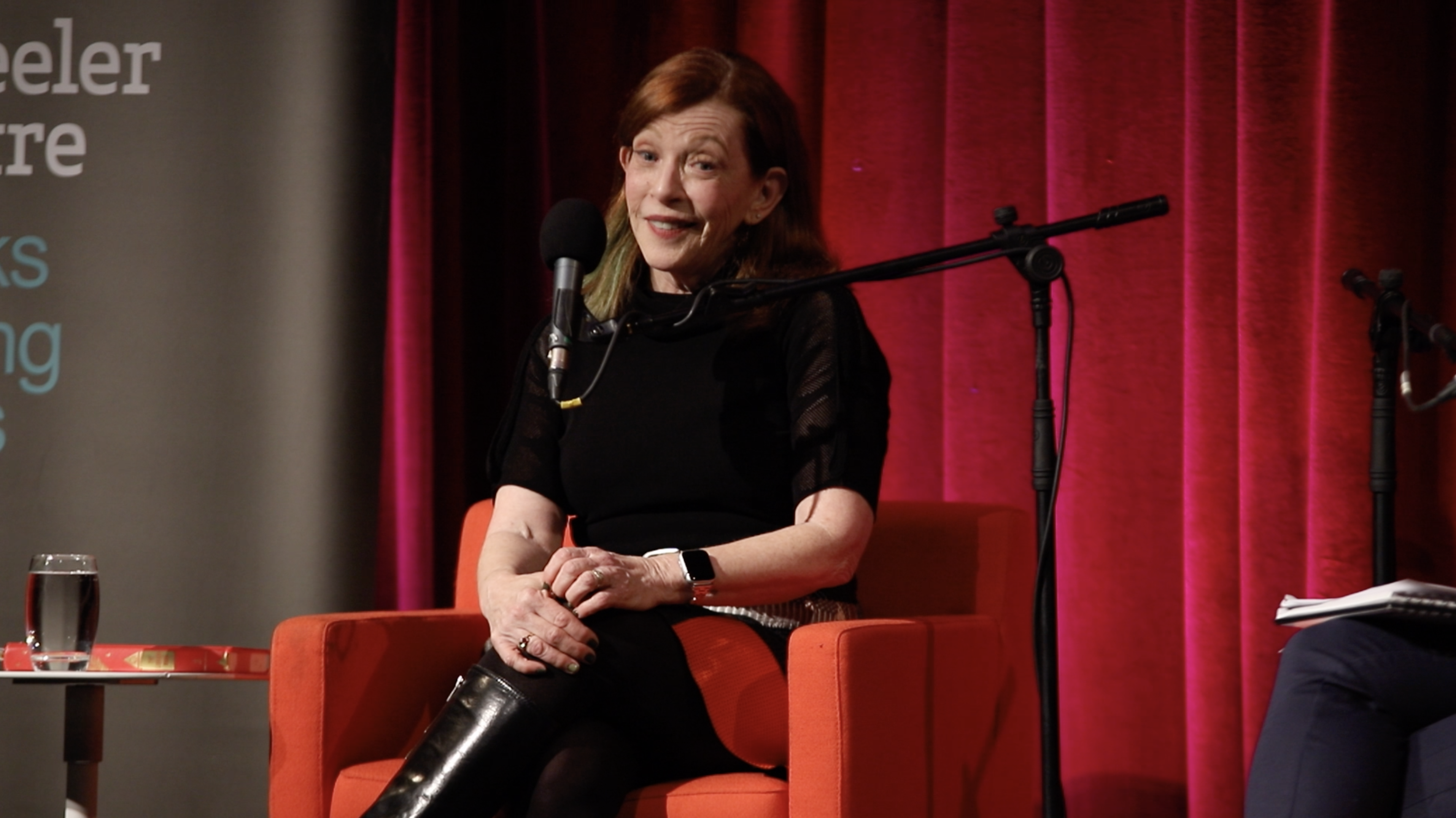 Photo of Susan Orlean, sitting on a red chair in front of a red curtain, hands resting on her knees