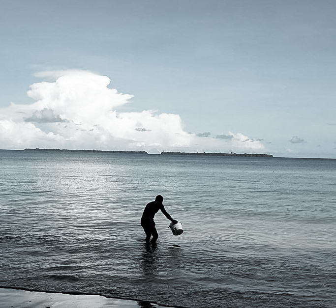 Photo of a man collecting sea water