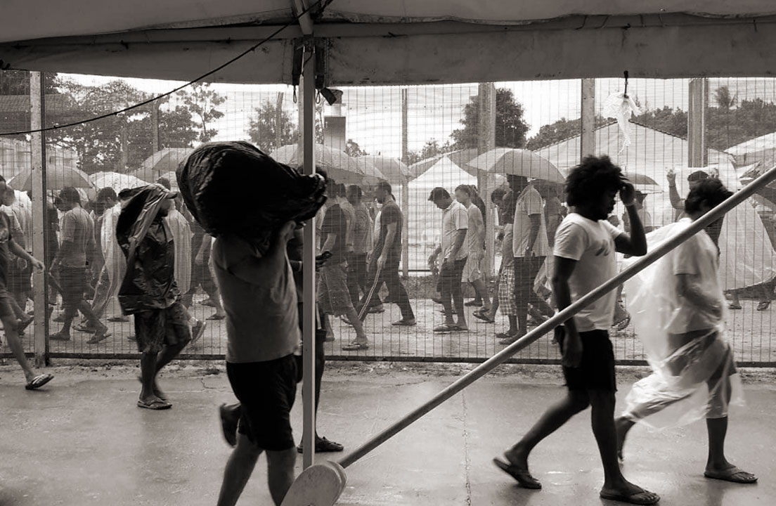 Photo of men sheltering from rain at Manus Island Regional Processing Centre