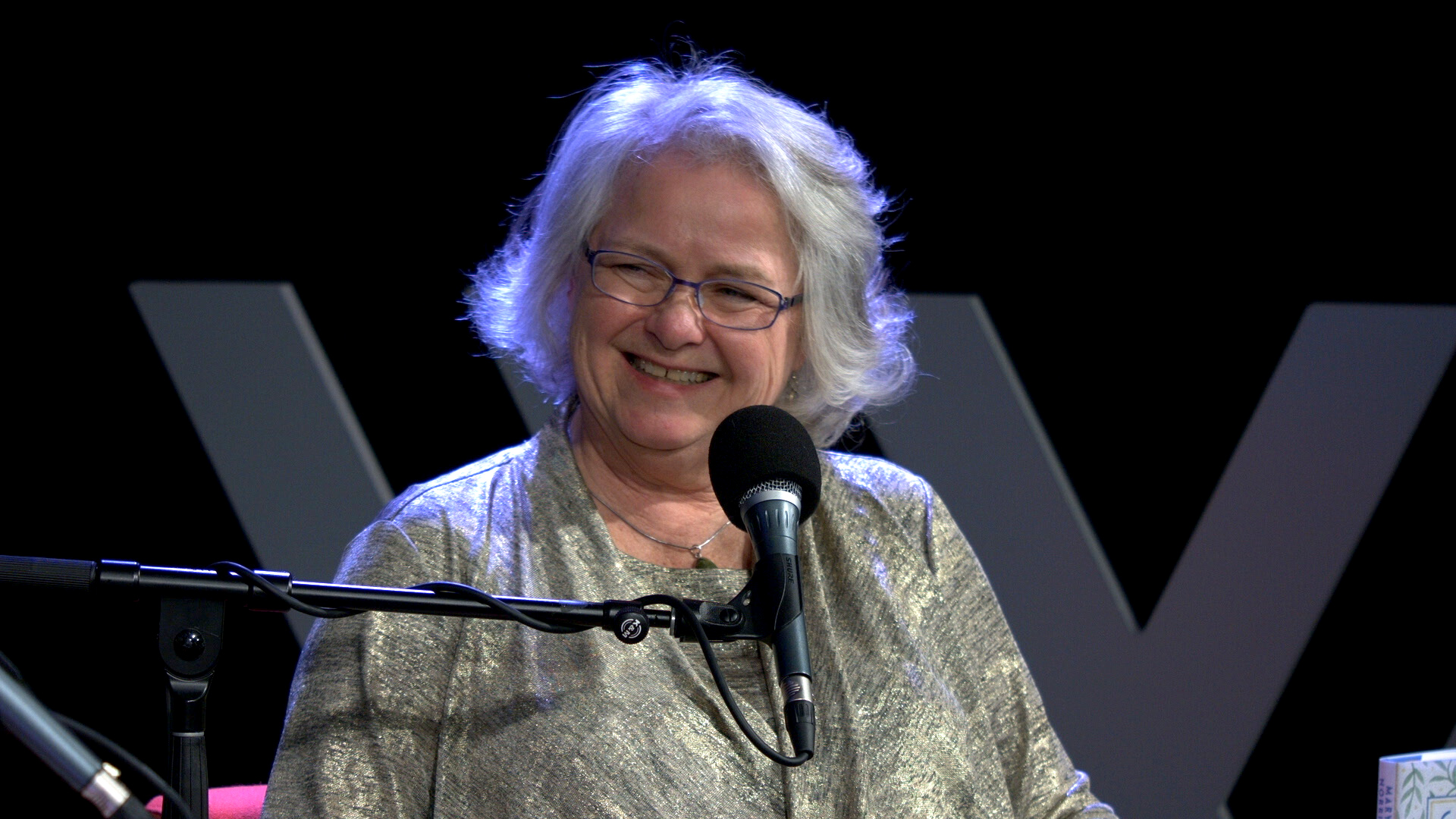 Photo of a woman with white, wavy hair – backlit with a purple glow – smiling in front of a microphone