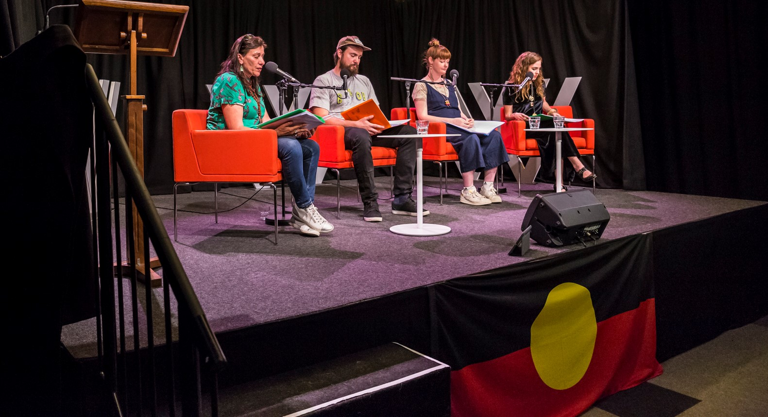 Photo of four people on stage, seated on red armchairs, with an Aboriginal flag attached to the front of the stage