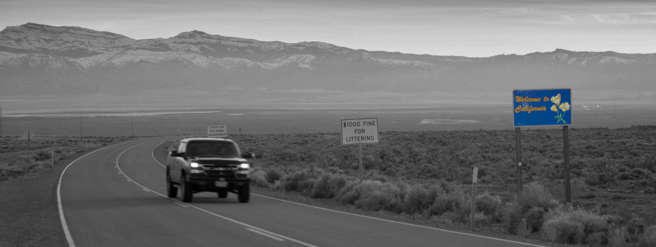 Black and white photograph of a highway in front of a mountain range, with a colour sign that says 'Welcome to California'