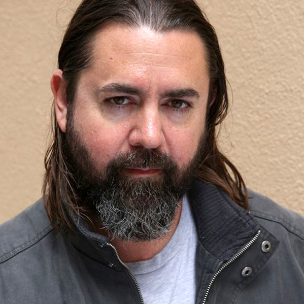 Photograph of a man with long brown hair and a beard, looking at the camera