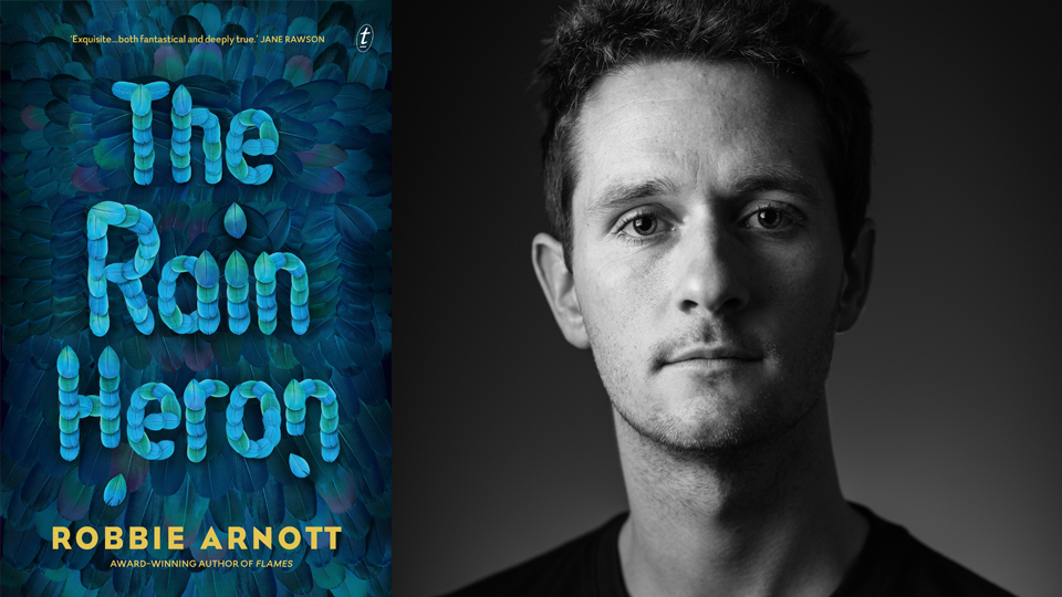 Photograph of Robbie Arnott next to the cover of his book, 'The Rain Heron', featuring the title spelled out using blue feathers