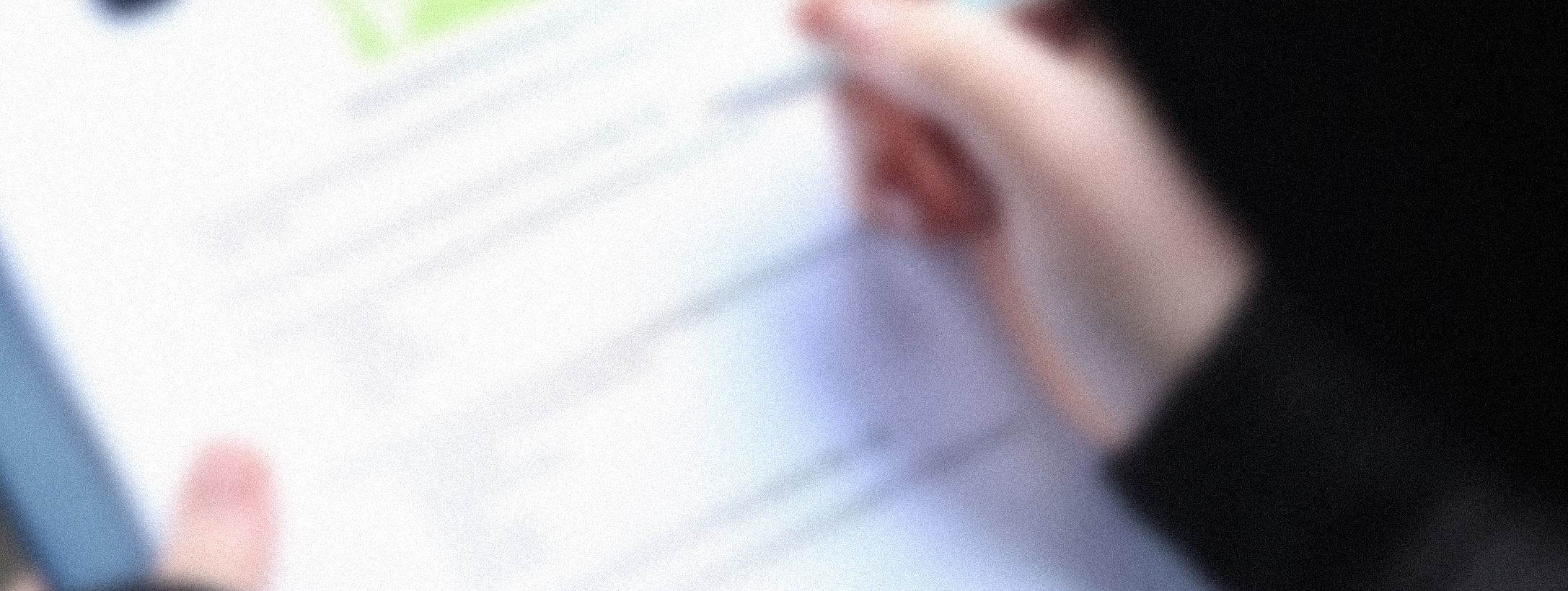 Photograph of a hand filling in a survey with a pen