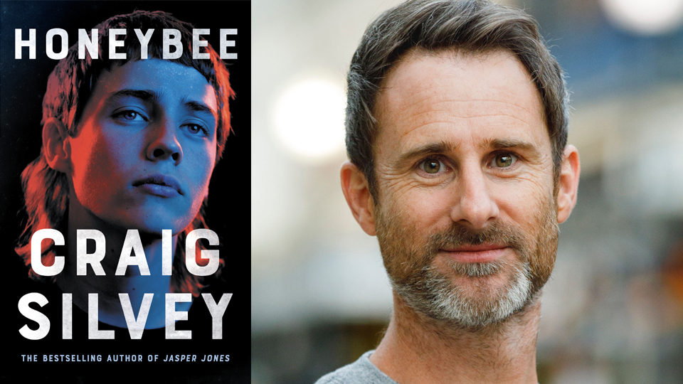 Photograph of Craig Silvey next to the cover of his book, 'Honeybee'