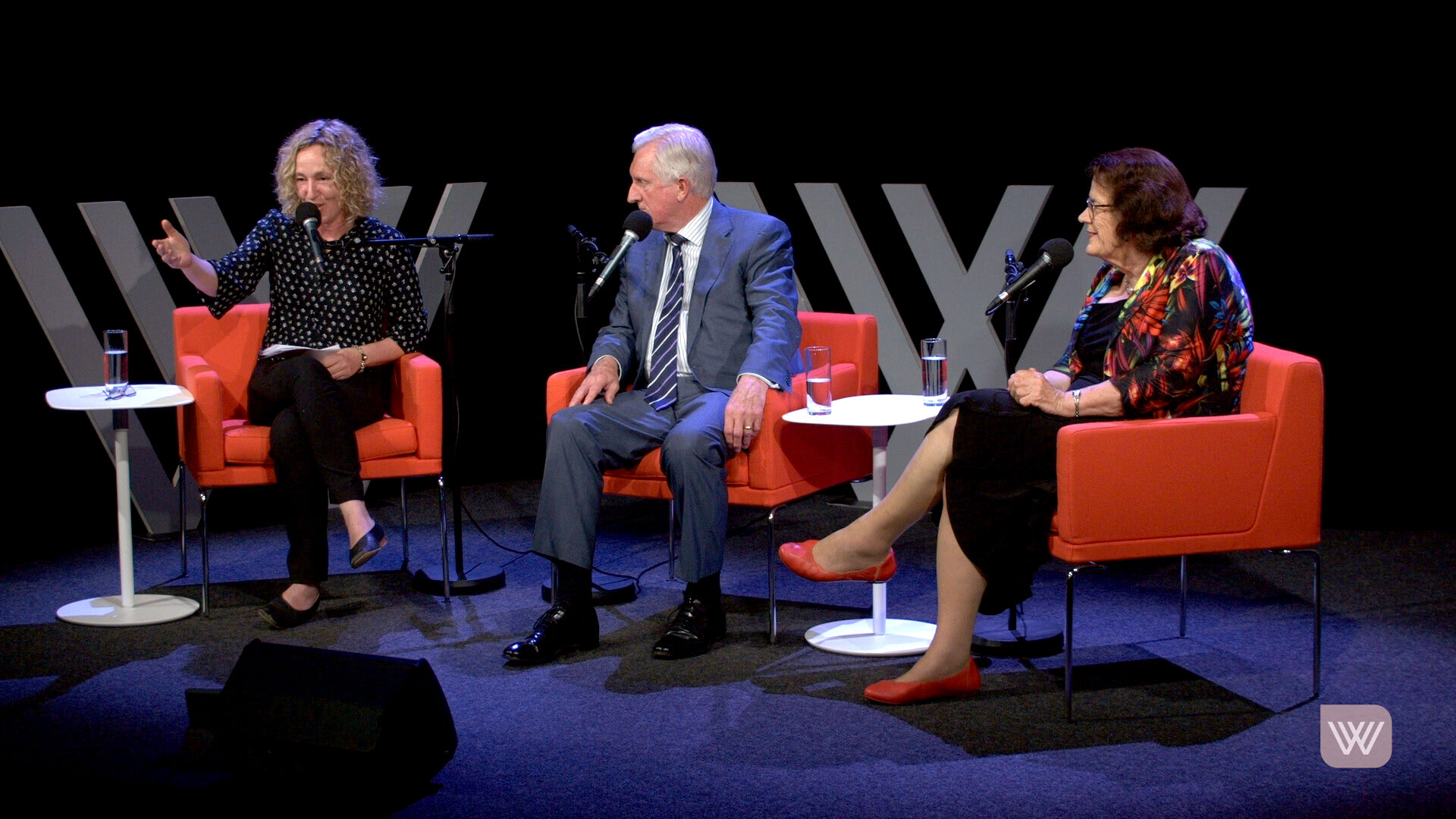 Photo of Sally Warhaft (speaking into her microphone), John Hewson and Michelle Grattan - on a grey stage, sitting on red armchairs