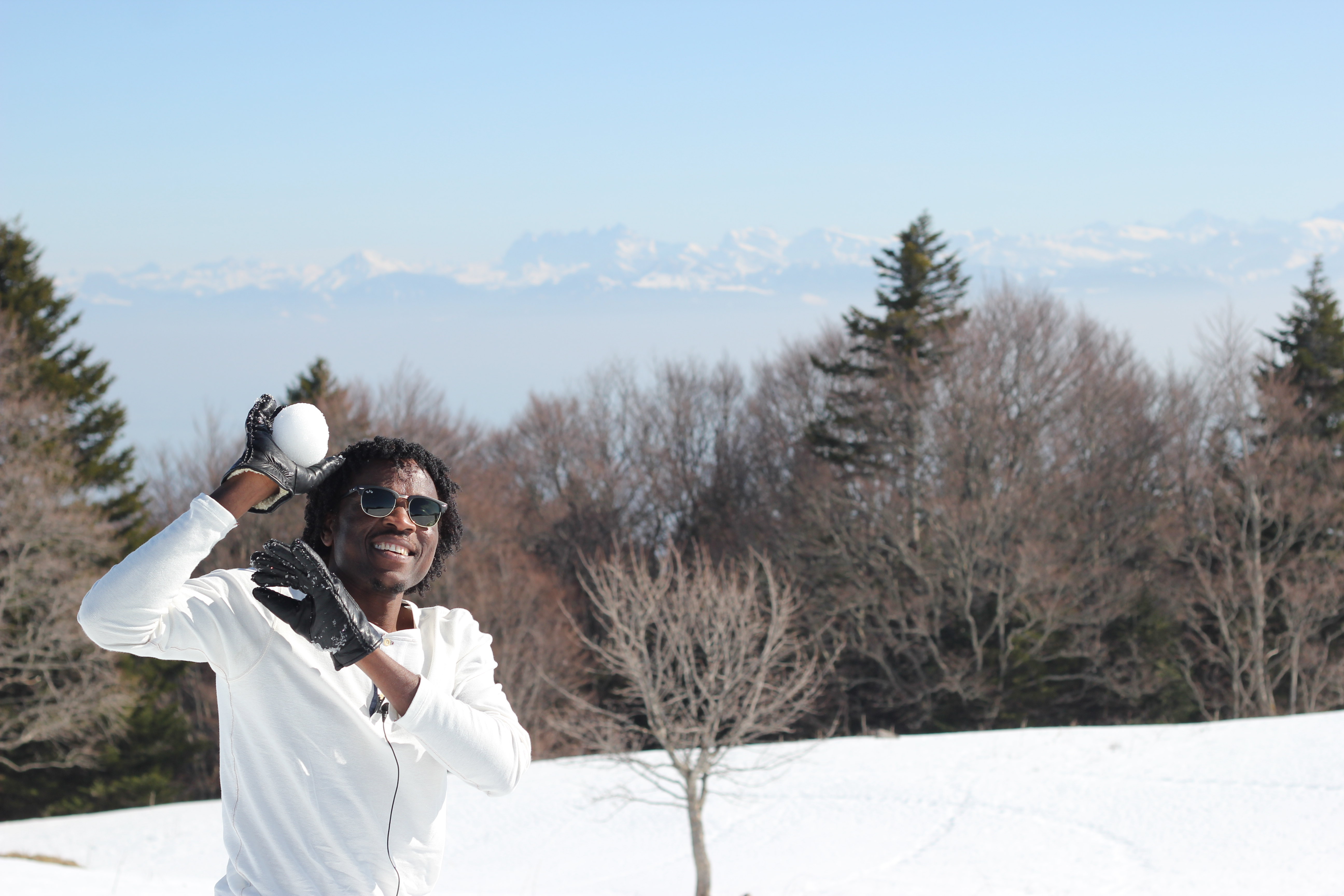 Aziz in the snow – wearing a white shirt, black gloves and sunglasses – about to throw a snowball