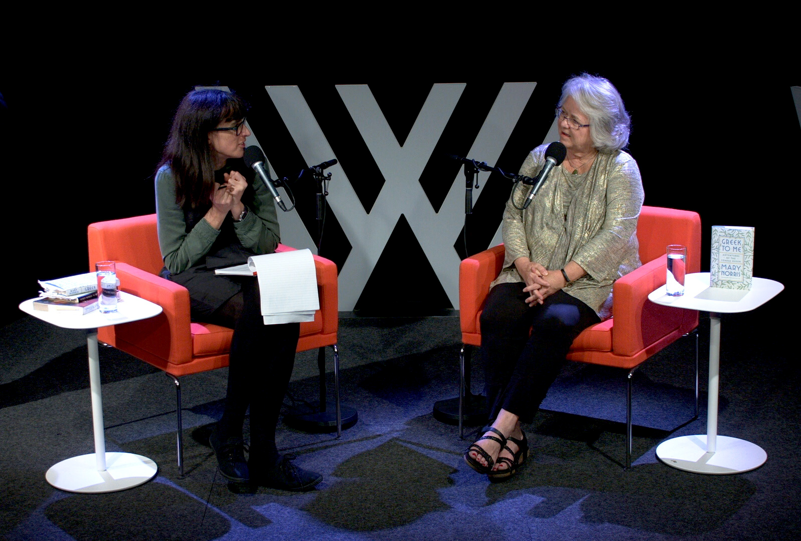Two women sitting on red chairs with microphones, on the Wheeler Centre stage