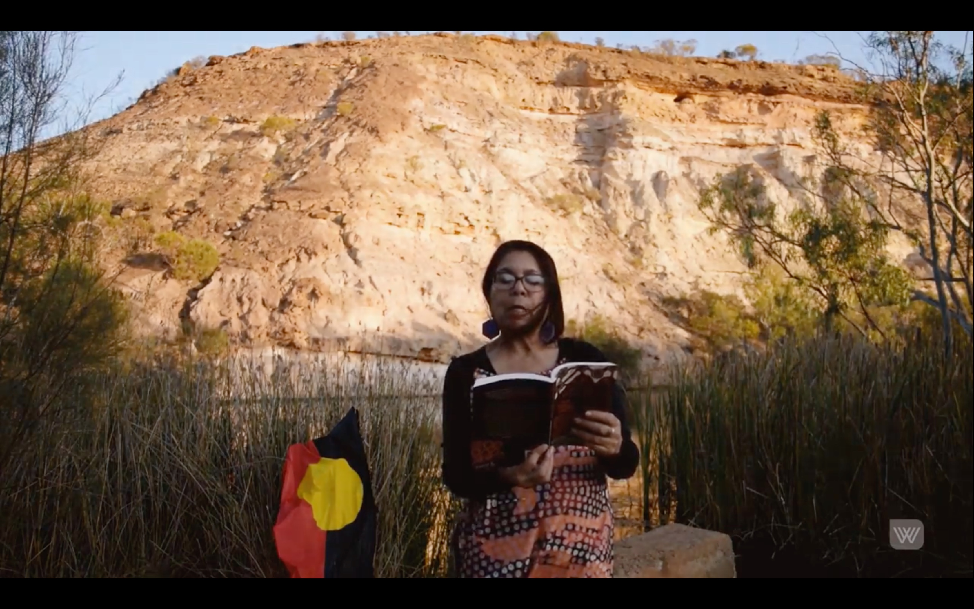 Still image of Charmaine Papertalk Green reading on Country