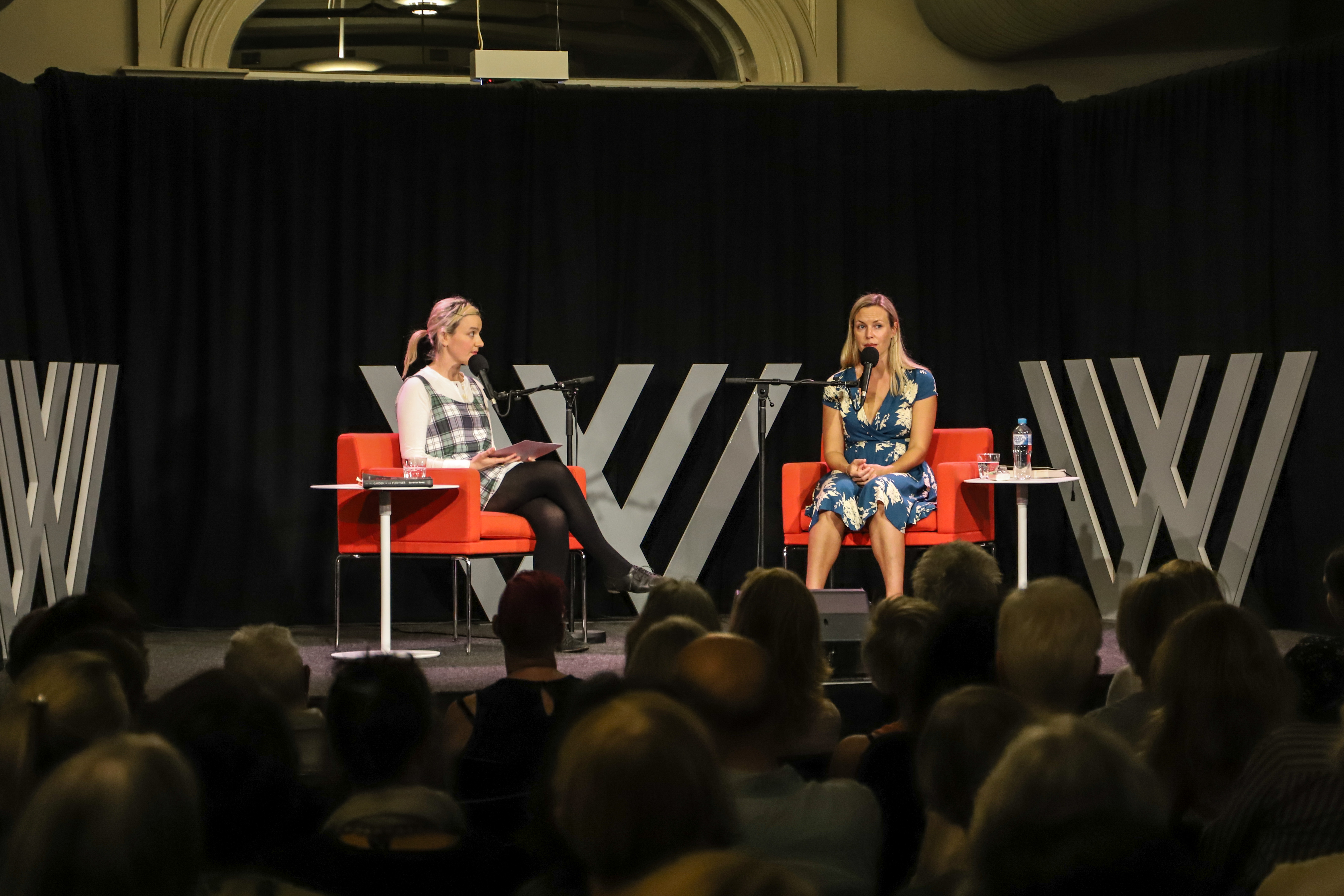 Photo of Abigail Ulman and Ceridwen Dovey talking on the Wheeler Centre stage – red chairs with white side tables, and black curtains with large silver Wheeler Centre logo displays against them