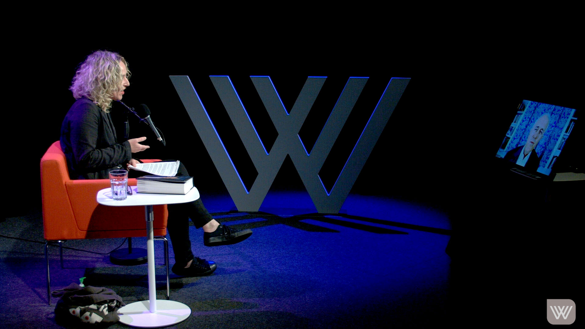Photo of Sally Warhaft on the Wheeler Centre stage, speaking whilst facing a screen with Malcolm Turnbull's face –as he appears via video-link