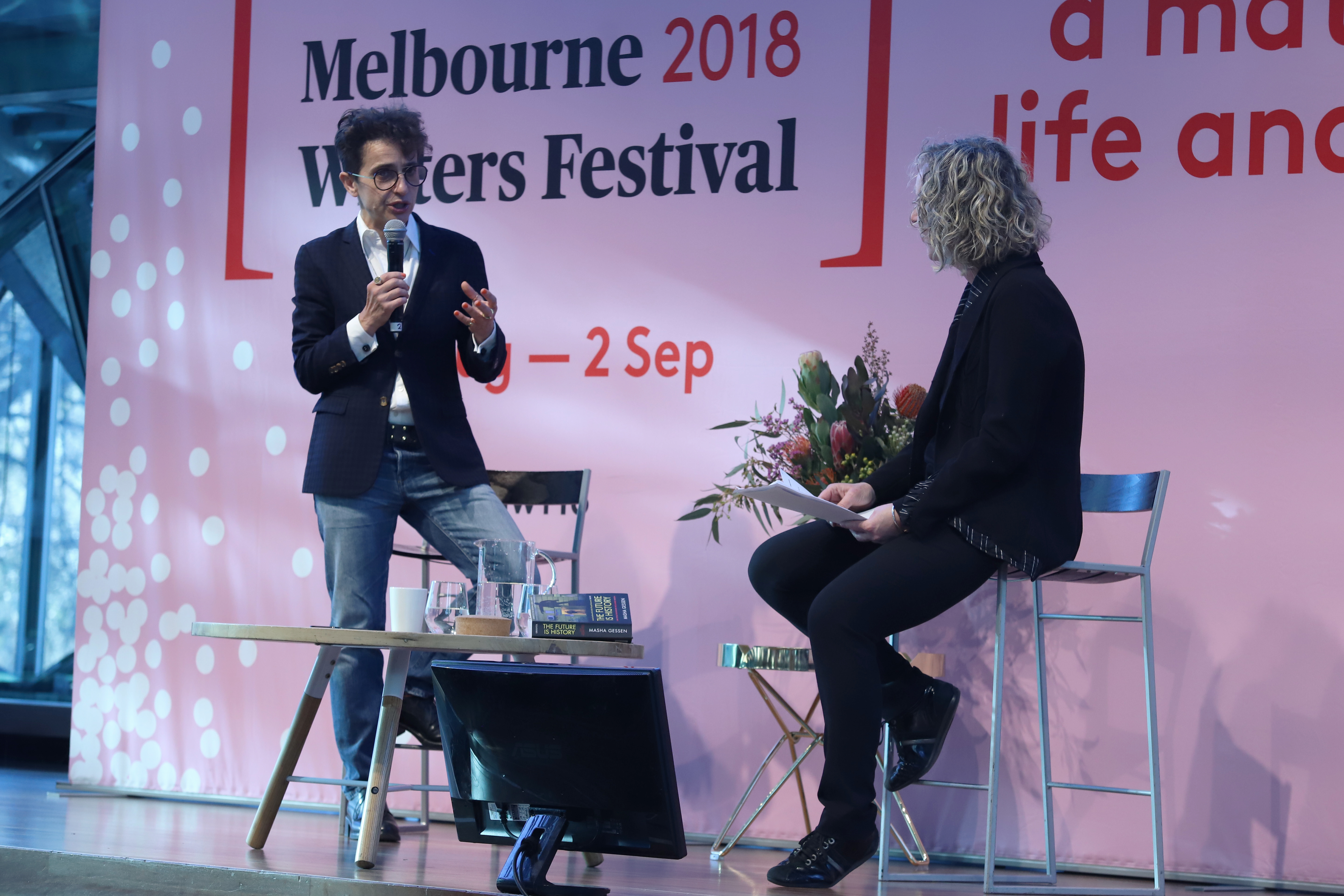 Photo of two people standing in front of a Melbourne Writers Festival banner. On the left, Masha Gessen is wearing glasses with short brown curly hair, holding a microphone and speaking. Sally Warhaft is seated on a stool beside her