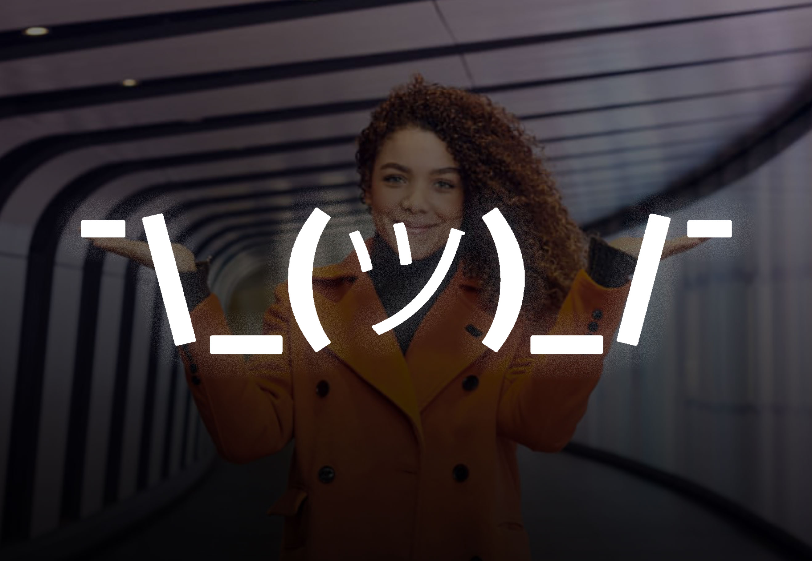 Overlaid 'shruggie' emoticon on the 2019 International Women's Day campaign image, which depicts a woman holding her palms up to form a 'w' shape with her body