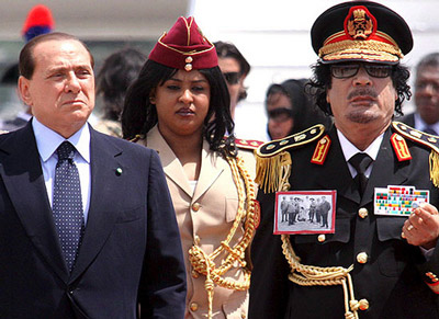 Colonel Gaddafi on a 2009 state visit to Italy, alongside one of his military advisers and Italian President Berlusconi, via Libero Liberos/Flickr