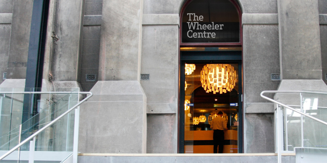 Photo of a grey stone building and a glass doorway leading to the Wheeler Centre's reception area, with the text 'The Wheeler Centre' written across the top