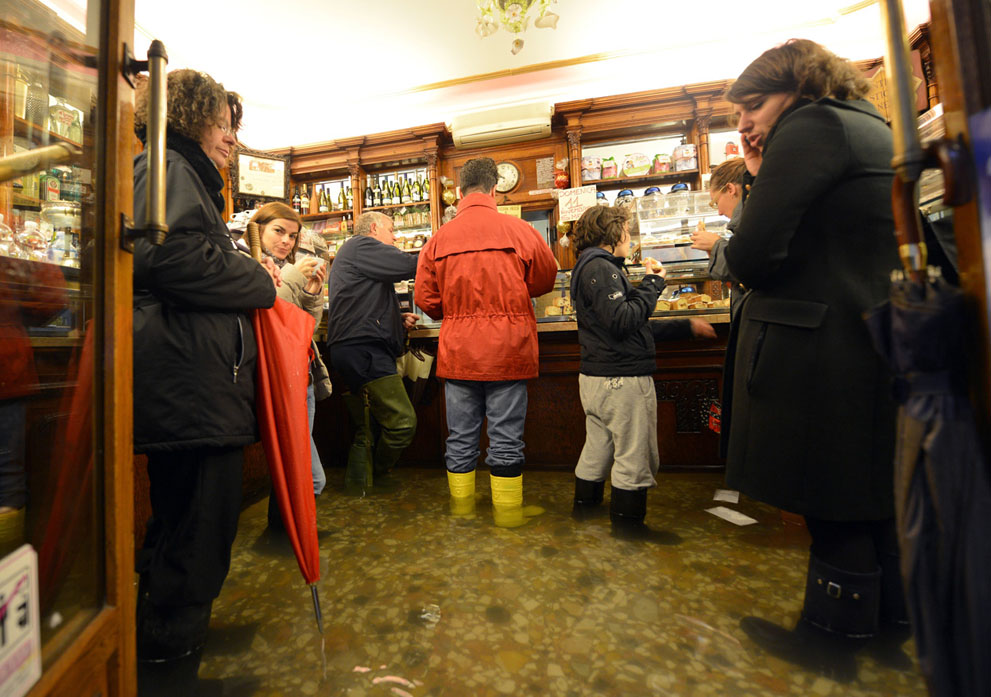 People order coffee in a flooded Venice shop.