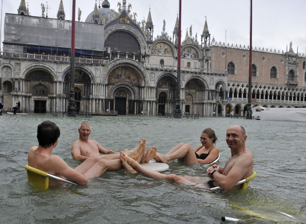 In this photo, taken in the past week, people sit at a table in a flooded Piazza San Marco in Venice.
