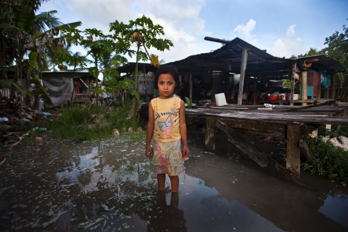 Teuga Patolo stands in king-tide waters that surround her neighbour's house. Oxfam: Rodney Dekker