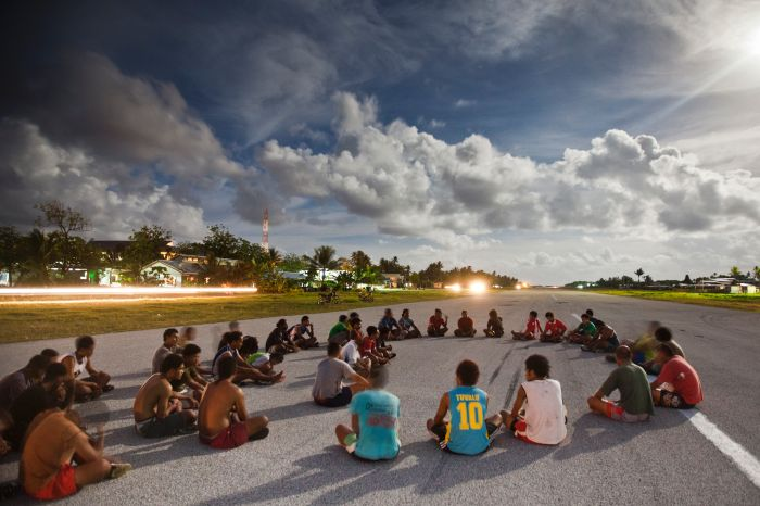 In the late afternoon, people gather and play sport on the airport runway at Funafui in Tuvalu. When king tides occur, sections of the runway are flooded. Oxfam: Rodney Dekker